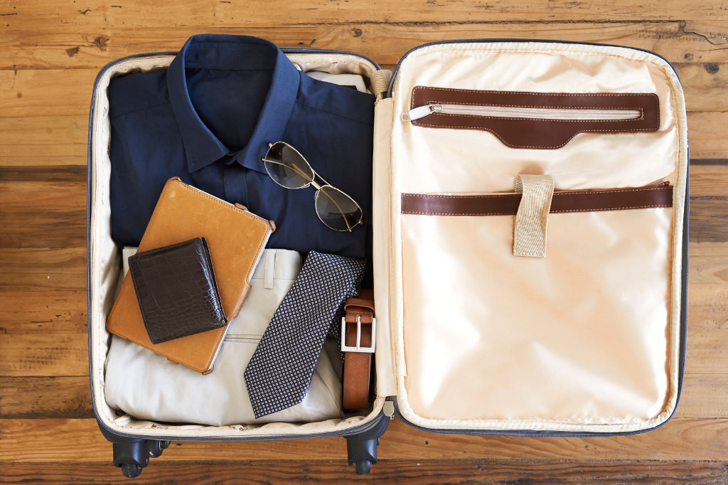 High angle shot of a suitcase packed with various essentials for a traveling businessman